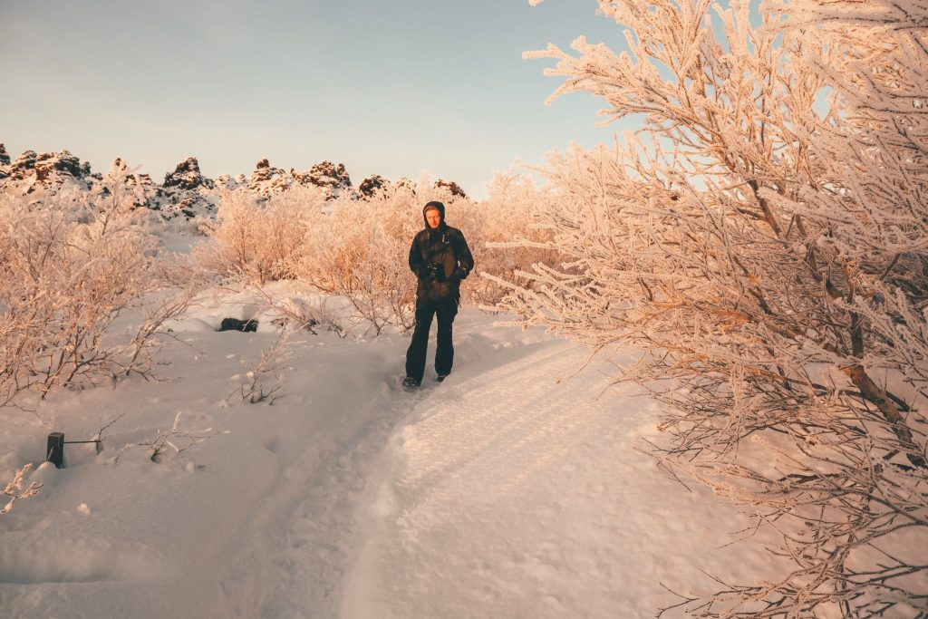 man walking through the snow in Iceland on a budget