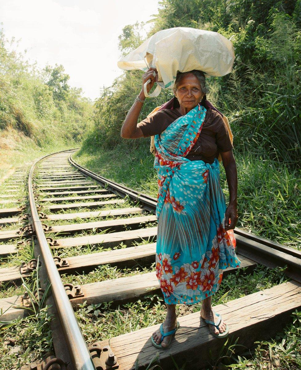 PORTRAIT OF A WOMAN CARRYING TEA ON HER HEAD IN ELLA, SRI LANKA