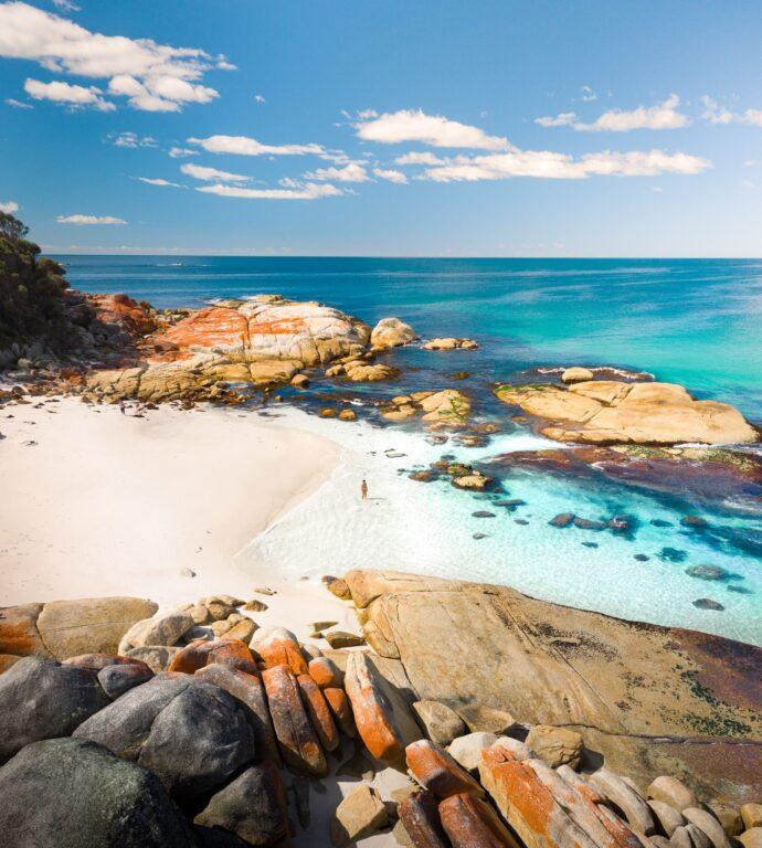 ORANGE ROCKS AND BLUE WATER AT BAY OF FIRES TASMANIA